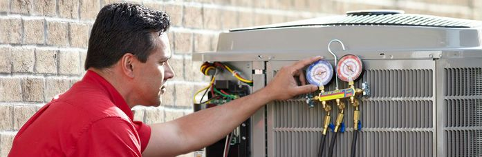 HVAC technician checking gauge of air conditioner